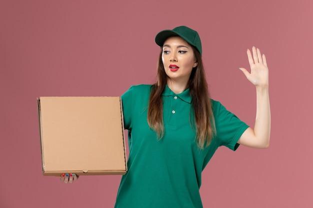 Vue de face femme courrier en uniforme vert tenant la boîte de nourriture sur la livraison uniforme de service de travailleur mural rose clair