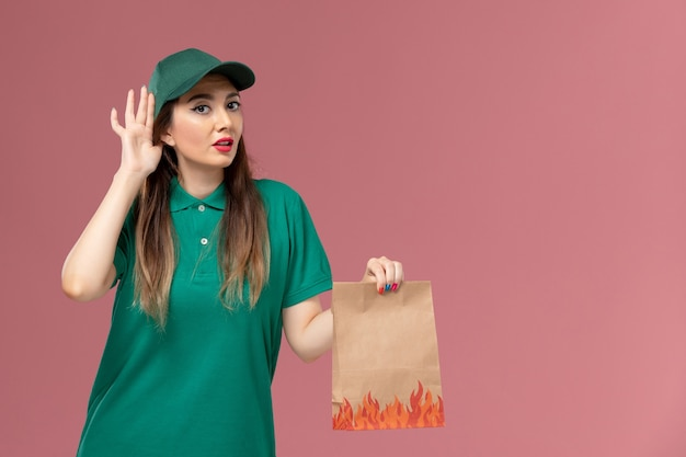 Vue de face femme courrier en uniforme vert tenant un paquet alimentaire papier essayant d'entendre sur la livraison uniforme de service de mur rose