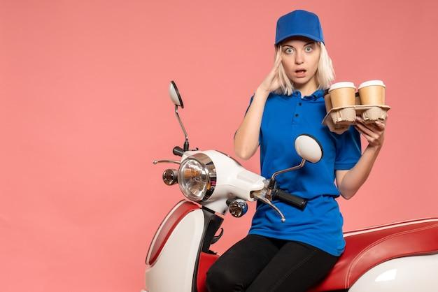 Vue de face femme courrier sur vélo avec tasses à café sur le rose