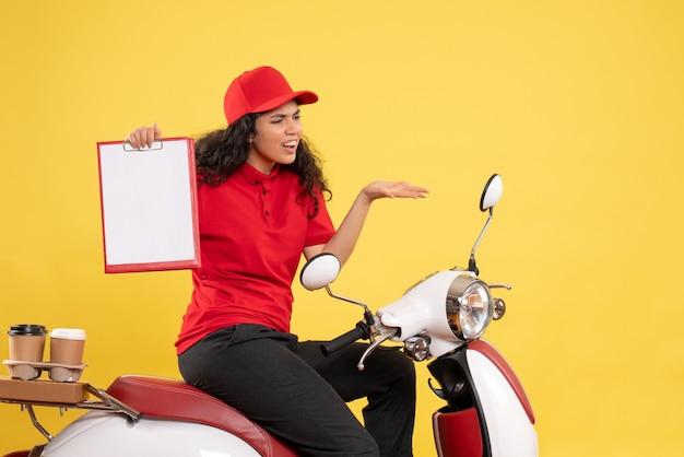 Vue de face femme coursier à vélo pour la livraison de café sur fond jaune livraison uniforme travail travailleur service travail femme nourriture