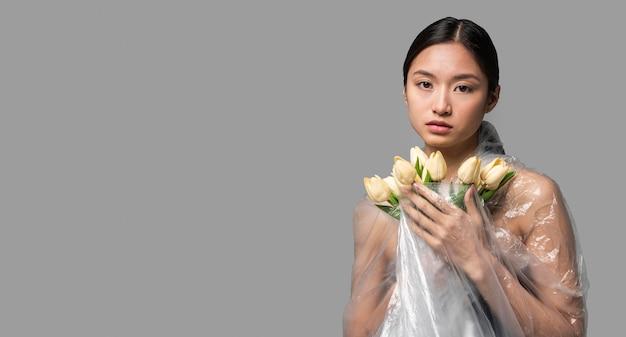 Vue de face femme couverte de plastique tenant un bouquet de fleurs