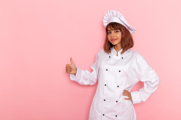 Vue de face femme cuisinier en costume de cuisinier blanc posant sur une surface rose clair