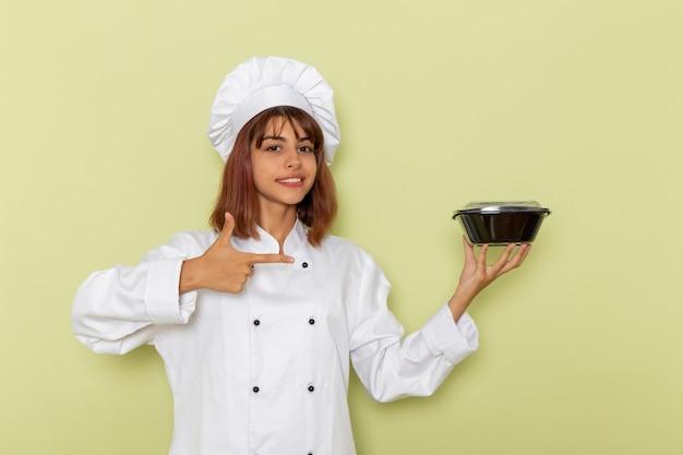 Vue de face femme cuisinier en costume de cuisinier blanc tenant un bol sur une surface vert clair