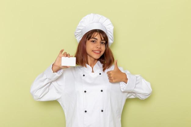Vue de face femme cuisinier en costume de cuisinier blanc tenant une carte blanche sur une surface vert clair