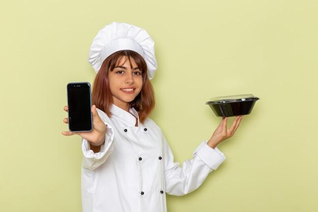 Vue de face femme cuisinier en costume de cuisinier blanc tenant le téléphone et bol noir sur la surface verte