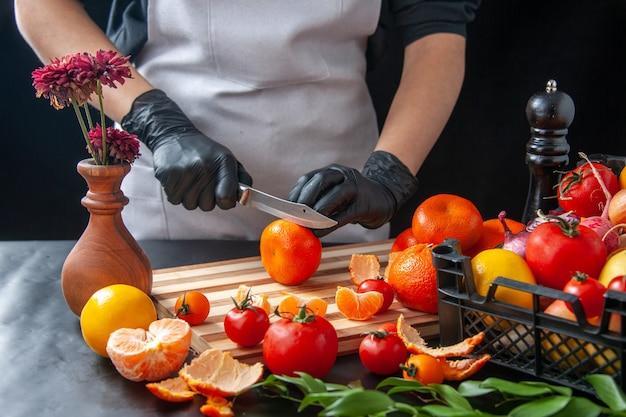 Vue de face femme cuisinier coupant des mandarines sur une salade de cuisson sombre régime de santé repas de légumes nourriture travail de fruits