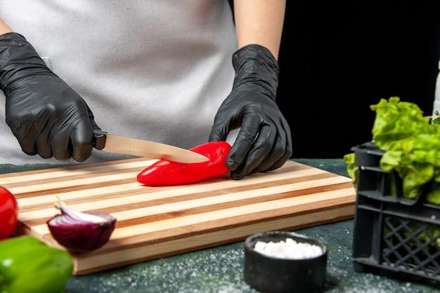 Vue de face femme cuisinier coupant le piment rouge sur la nourriture grise cuisine salade cuisine repas de cuisine
