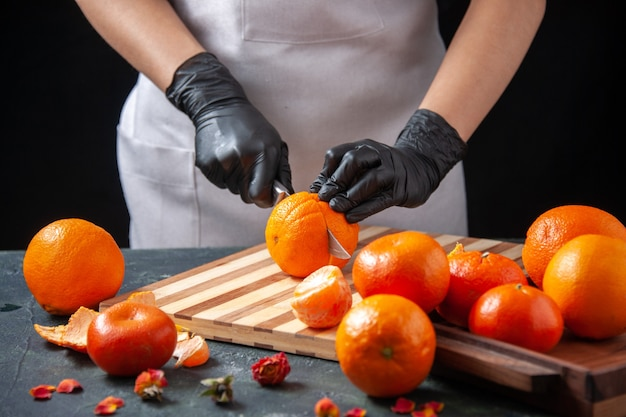 Vue de face femme cuisinier coupe orange sur salade sombre repas santé travail alimentaire légume boisson fraîche régime de fruits