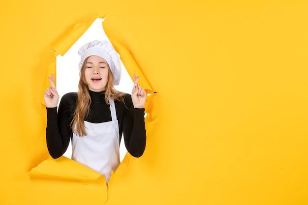 Vue de face femme cuisinier avec les doigts croisés sur papier de couleur jaune soleil travail alimentaire photo émotion
