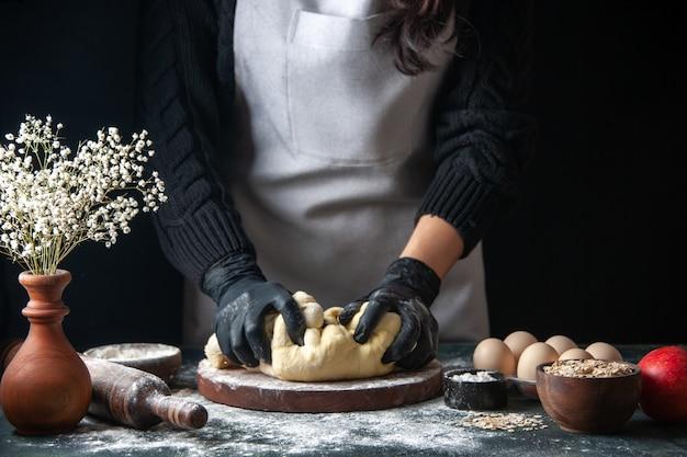 Vue de face femme cuisinier étaler la pâte sur le travail de la pâtisserie sombre four à tarte à la pâte crue