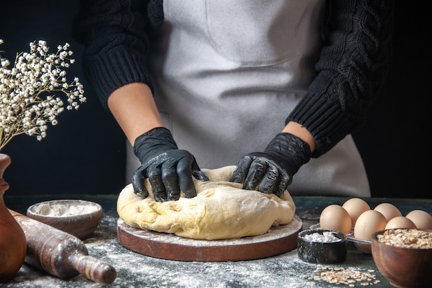 Vue de face femme cuisinier étaler la pâte sur le travail de pâtisserie sombre pâte crue four à tarte boulangerie hotcake