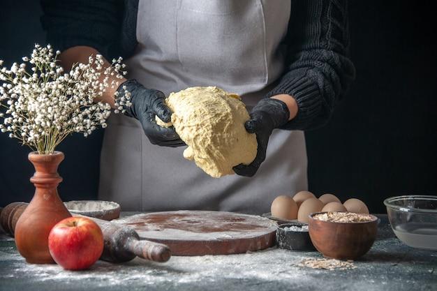 Vue de face femme cuisinier étaler la pâte sur le travail sombre pâte crue four à tarte pâtisserie hotcake boulangerie oeuf