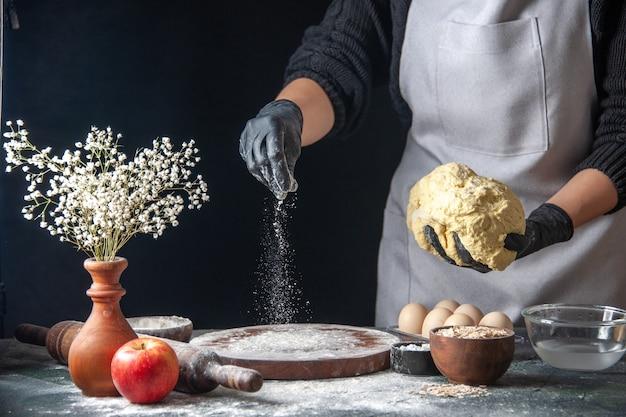 Vue de face femme cuisinier étaler la pâte sur un travail sombre pâte crue tarte four pâtisserie hotcake boulangerie oeufs