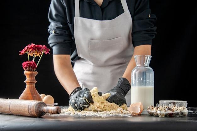 Vue de face femme cuisinier étaler la pâte sur le travail sombre pâtisserie tarte boulangerie cuisson biscuit pâte cuire au four