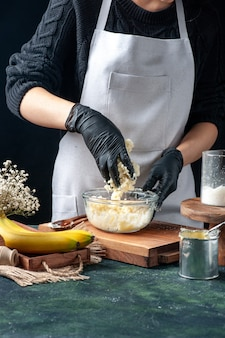 Vue de face femme cuisinier faisant des bonbons à la noix de coco à partir de lait concentré sur fond sombre