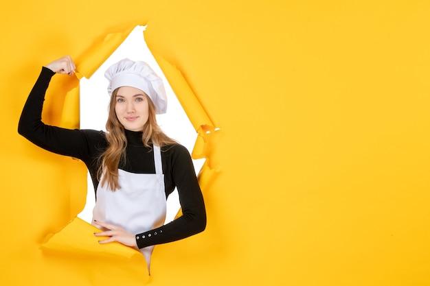 Vue de face femme cuisinier fléchissant et souriant sur jaune émotion couleur papier travail cuisine soleil nourriture photo