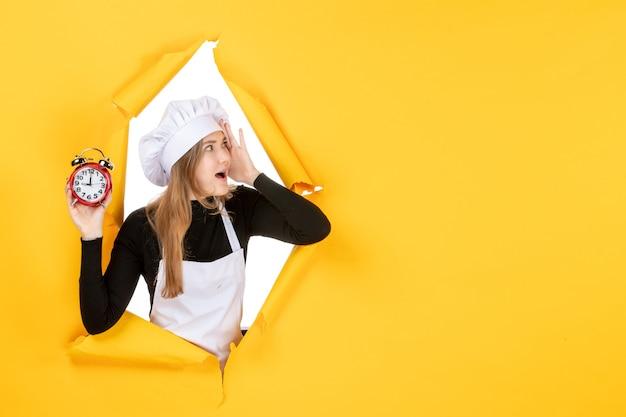 Vue de face femme cuisinier avec horloges sur temps jaune nourriture photo couleur travail cuisine émotion soleil cuisine