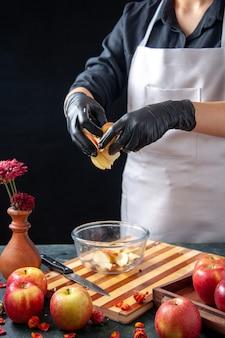 Vue de face femme cuisinier mettant des pommes dans une assiette sur jus de fruits noirs régime alimentaire salade repas travail exotique tarte gâteaux