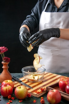 Vue de face femme cuisinier mettant des pommes dans une assiette sur jus de fruits noirs régime tartes salade de couleur repas alimentaire travail exotique gâteau
