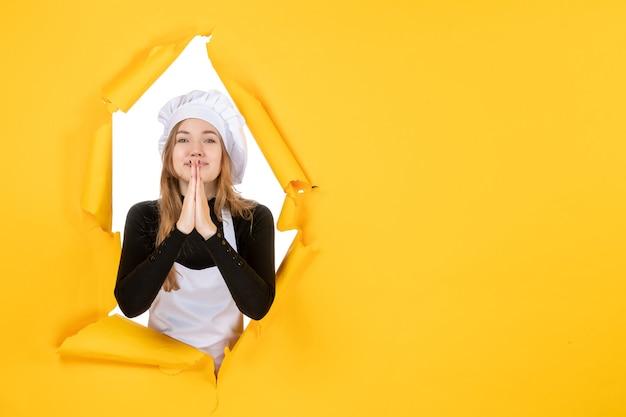 Vue de face femme cuisinier sur papier de couleur jaune soleil travail photo cuisine émotion alimentaire