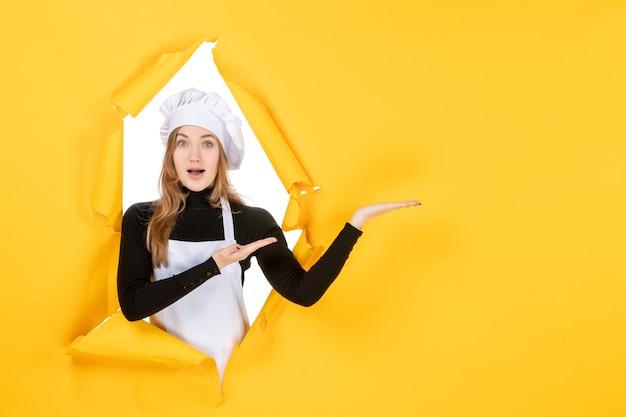 Vue de face femme cuisinier sur photo jaune cuisine alimentaire travail couleur papier soleil