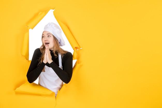Vue de face femme cuisinier priant sur papier de couleur jaune soleil travail photo cuisine émotion alimentaire