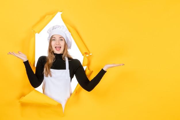 Vue de face femme cuisinier sur sol jaune photo soleil cuisine travail couleur cuisine papier alimentaire