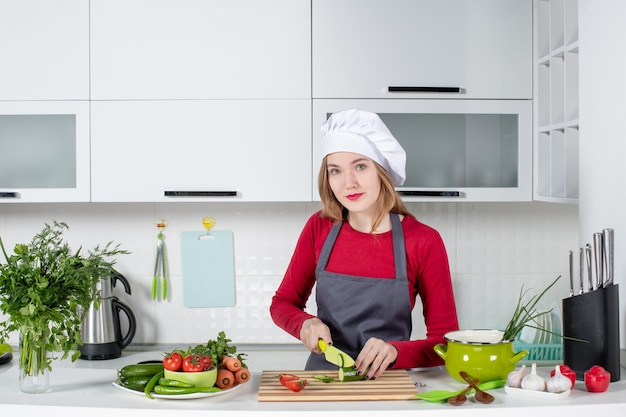 Vue de face femme cuisinier en tablier coupant le concombre tout en regardant à l'avant