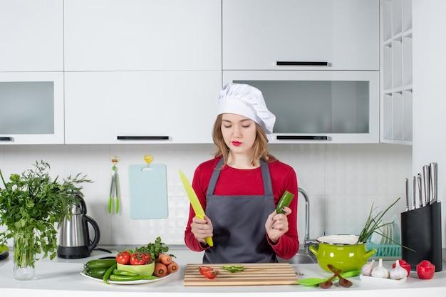 Vue de face femme cuisinier en tablier tenant un concombre et un couteau