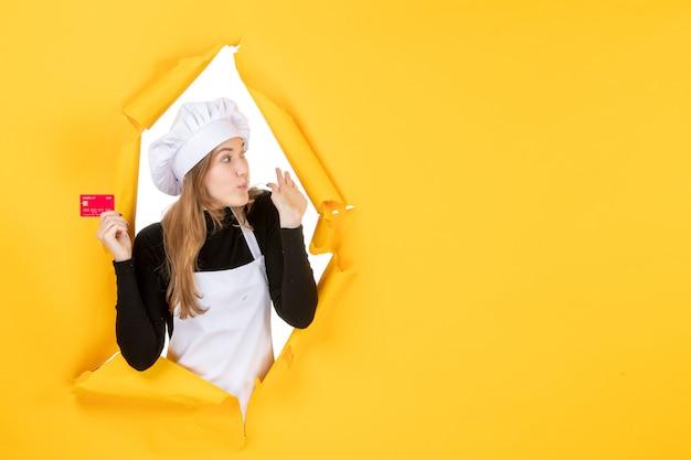 Vue de face femme cuisinier tenant une carte bancaire rouge sur argent jaune couleur travail photo cuisine cuisine émotion nourriture