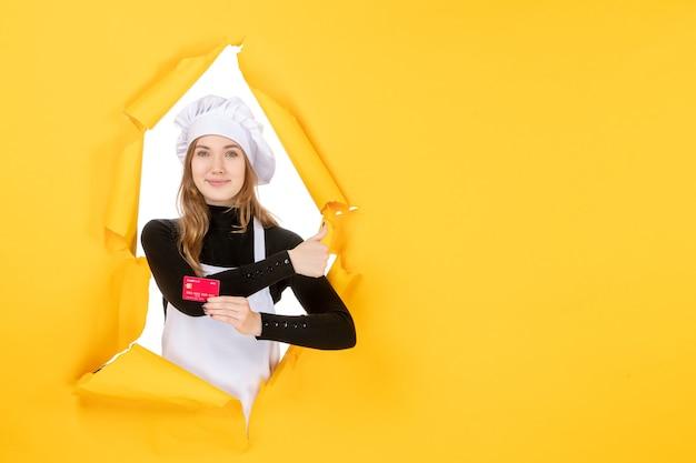 Vue de face femme cuisinier tenant une carte bancaire rouge sur photo jaune nourriture cuisine cuisine couleur argent travail