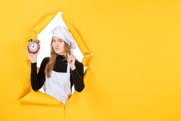 Vue de face femme cuisinier tenant des horloges sur la nourriture jaune photo couleur travail cuisine cuisine émotion soleil