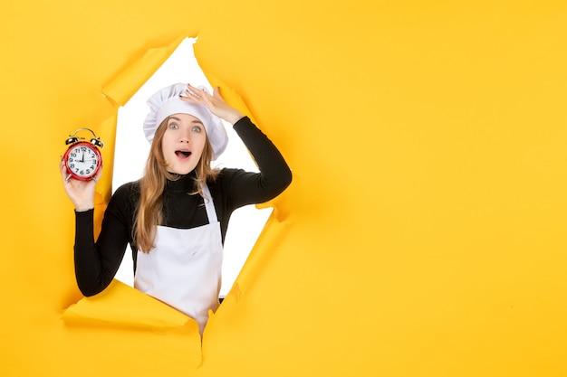 Vue de face femme cuisinier tenant des horloges sur le temps jaune nourriture photo travail cuisine émotion soleil cuisine couleurs