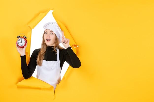 Vue de face femme cuisinier tenant des horloges sur le temps jaune travail alimentaire cuisine émotion soleil cuisine couleur