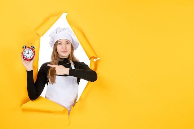 Vue de face femme cuisinier tenant des horloges sur le temps jaune travail photo cuisine émotions soleil cuisine couleur
