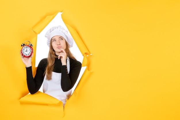 Vue de face femme cuisinier tenant des horloges sur le temps jaune travail photo émotion cuisine soleil cuisine couleur