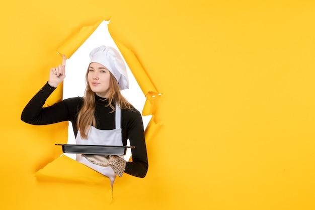 Vue de face femme cuisinier tenant pan noir sur jaune émotion alimentaire travail photo cuisine cuisine couleur