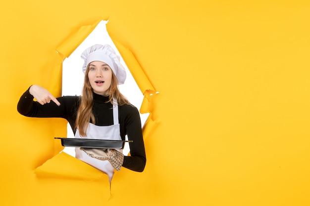 Vue de face femme cuisinier tenant pan noir sur jaune émotion soleil nourriture photo travail cuisine couleur