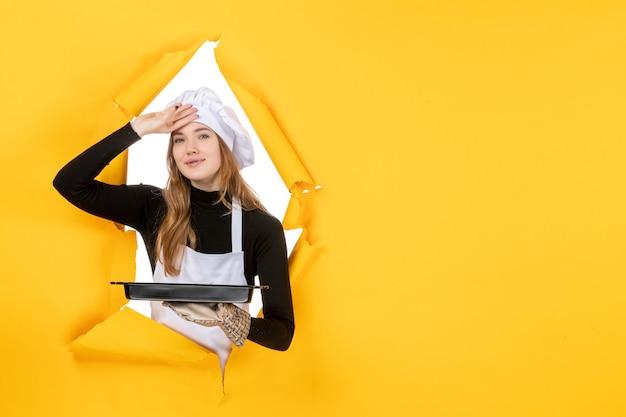 Vue de face femme cuisinier tenant pan noir sur jaune émotion soleil travail photo cuisine cuisine couleur