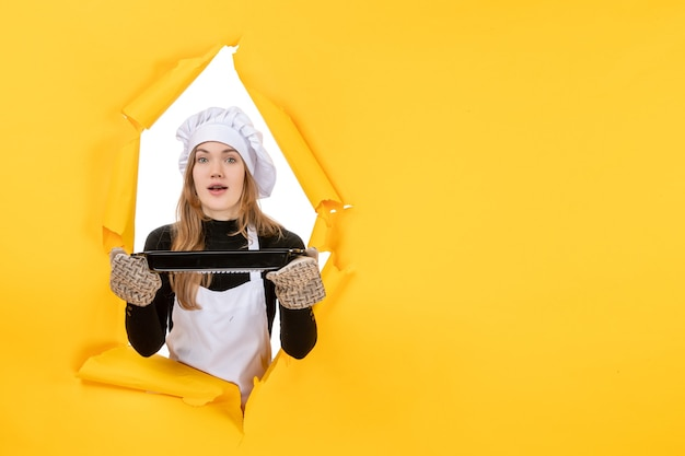Vue de face femme cuisinier tenant pan noir sur jaune soleil temps nourriture photo cuisine émotion cuisine couleur