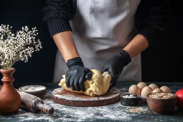 Vue de face femme cuisinière étaler la pâte sur un travail sombre pâte crue boulangerie pâtisserie tarte au four