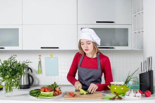 Vue de face femme cuisinière occupée en tablier coupant le concombre