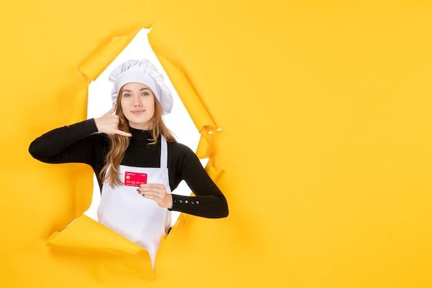 Vue de face femme cuisinière tenant une carte bancaire rouge sur un travail jaune photo émotion cuisine couleur argent cuisine