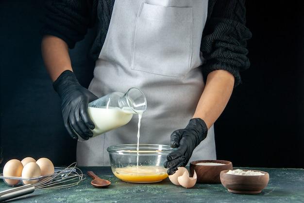 Vue de face femme cuisinière versant du lait dans des œufs sur une pâtisserie sombre tarte travailleur pâte cuisine travail hotcakes