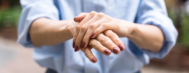 Vue de face femme désinfectant ses mains à l'extérieur