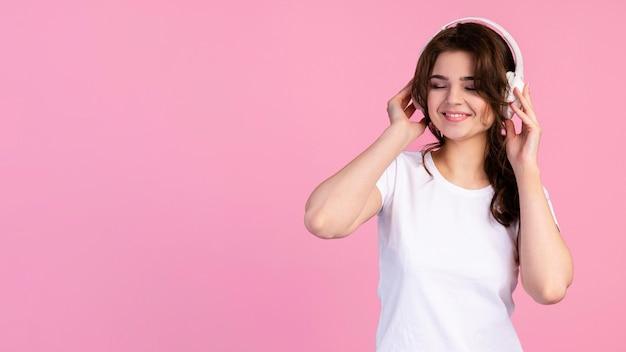 Vue de face de la femme écoutant de la musique sur des écouteurs avec espace de copie