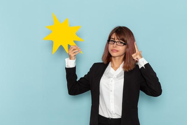 Vue de face femme employé de bureau en costume strict tenant grand panneau jaune sur une surface bleu clair