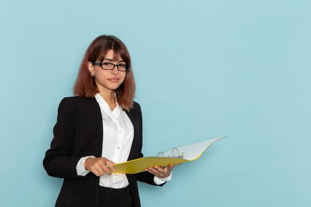 Vue de face femme employé de bureau tenant des documents jaunes sur la surface bleu clair