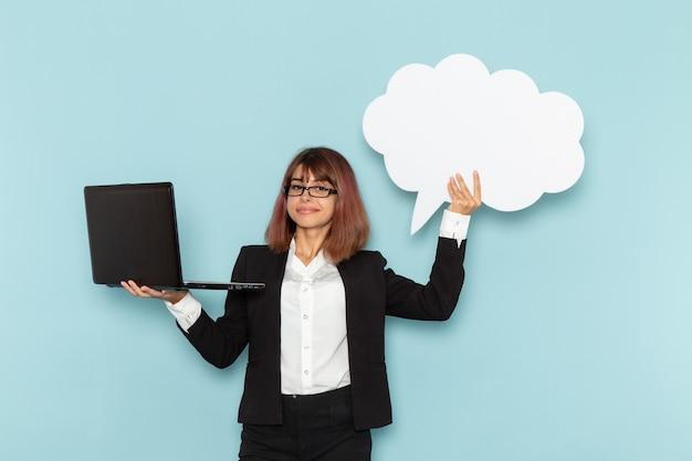 Vue de face femme employé de bureau tenant une pancarte blanche et un ordinateur portable sur la surface bleue
