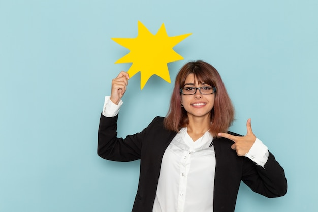 Vue de face femme employé de bureau tenant une pancarte jaune sur la surface bleue